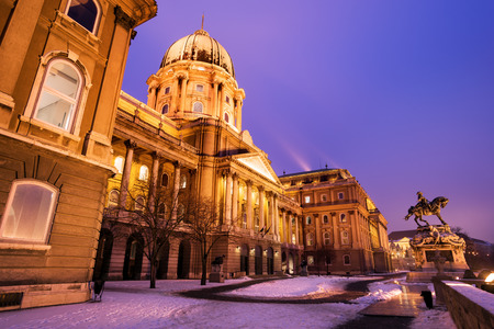 Snowy main facade of the historic Royal Palace - Buda Castle in Budapest under a purplish blue sky at nightfall - Hungary at night photo