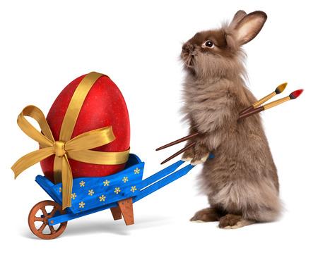Schattige paashaas konijn met een beetje blauwe kruiwagen en een rood paasei met een gouden lint, geïsoleerd op wit Stockfoto