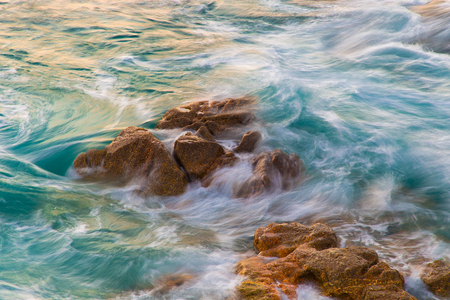 Captured motion of the sea waves crashing on the rocks near the shore in Orz�n Beach, A Coru� � a (Spain) Stock Photo - 95414193