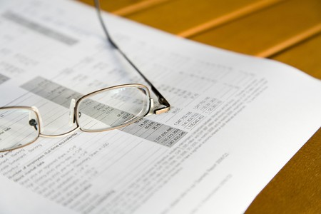 quarterly: Glasses on a quarterly report, shallow depth of field