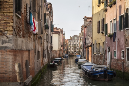 A quiet canal with boats in Venice, Italy, Southern Europe