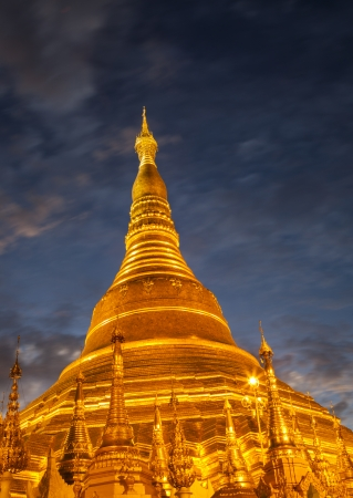The shiny golden Shwedagon Pagoda at dusk, 6s long exposure with blurred clouds in the night sky, Yangon, Myanmar, Southeast Asia