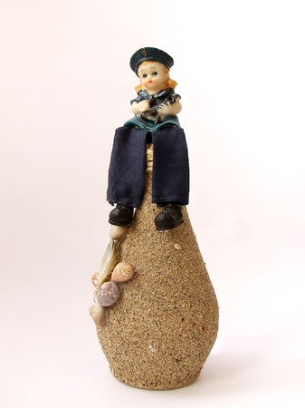 sailor girl: sailor girl figurine sitting on the decorative bottle covered with sand Stock Photo