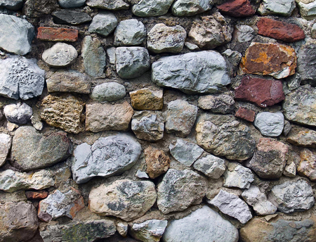 stonewall with various colors and shapes with cement mortar Stock Photo