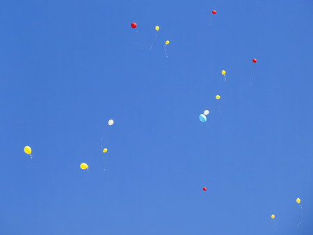many party  baloons flying in the blue sky