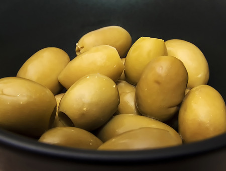 pitted: green olives in black bowl Stock Photo