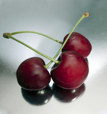 three cherries on a metal surface