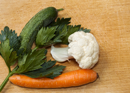 vegetables on a wooden cutting board - cucumber, cauliflower, carrots and celery leaf