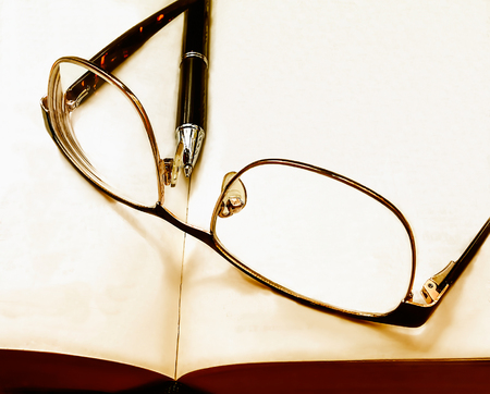 glasses and pen on the book left after learning