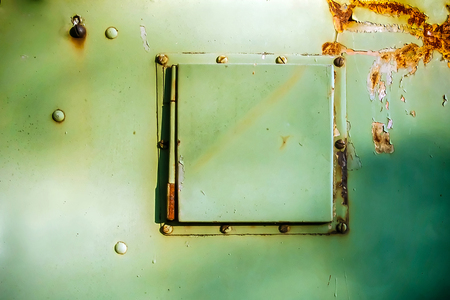 cover on hole in green, rusted metal container Stock Photo