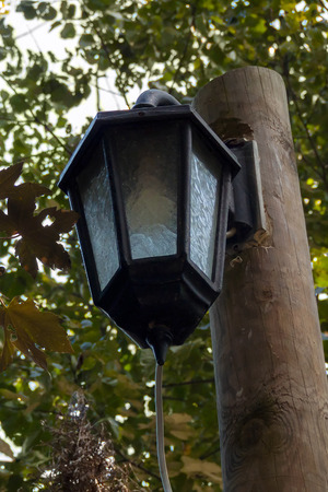 an old street lamp on a wooden pillar and electric cable Stock Photo