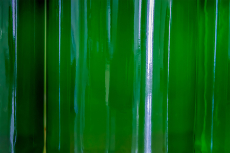 three full transparent green bottles that touch each other, through which the bends light - closeup