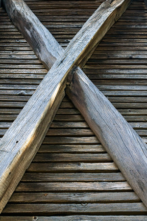 crossed wooden pillars, old granary structure vertical perspective
