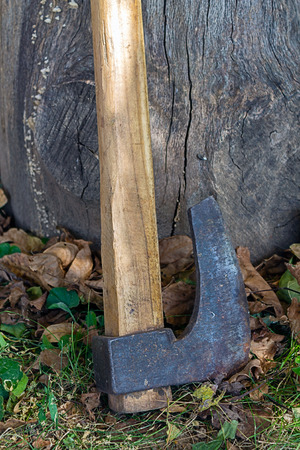 The ax is standing on the ground aside with the hive Stock Photo