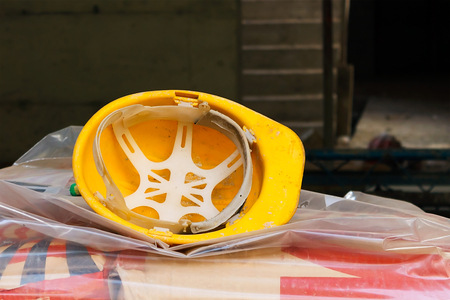 the used yellow protective helmet on the construction site left upside down on the cement bunch