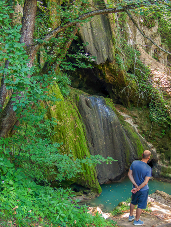a man standing next to the pond from the dried waterfall