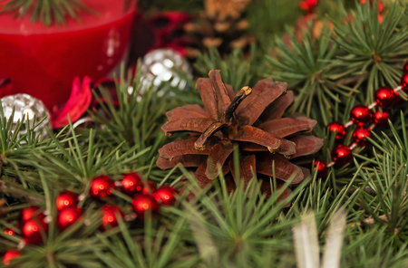 decoration with pinecone, pine branch, decorative balls and candle glass