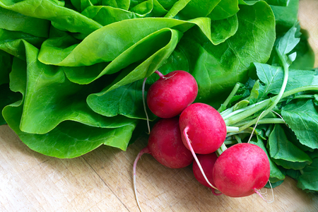 fresh vegetables on a wooden board - radishes, lettuce Stock Photo