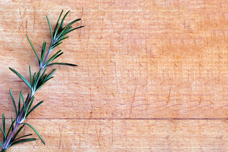 single small branch rosemary on a wooden cutting board