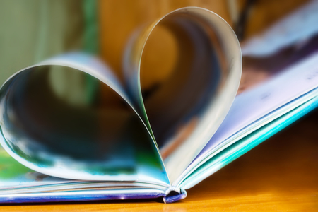 The blurring of the book opens on the desk, the pages rolls together to form a heart, shallow depth
