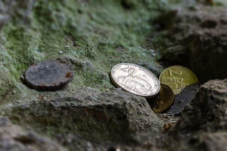 several Serbian, new and old corroded coins were left near a religious object on a moss stone Stock Photo