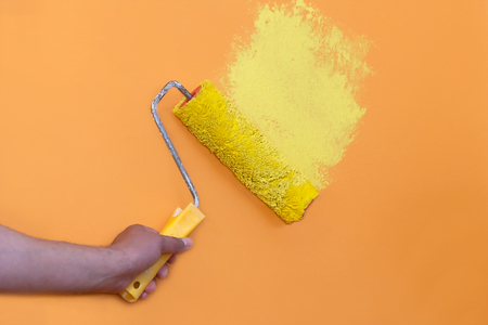 painter with roller in your hand painting with yellow paint over wall with peach color Stock Photo
