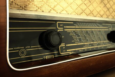 Old radio from the 60s, in a wooden box with traces of use and past time.Shallow depth, nostalgic look.