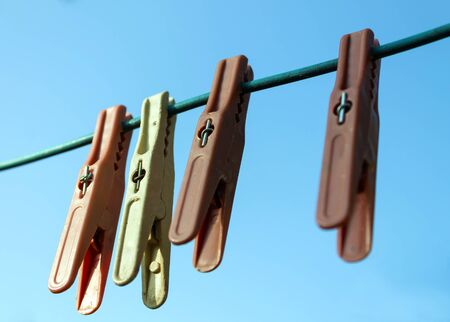 old colored clothespins hanging on a wire for drying clothes, blue sky in the background