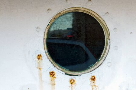 Vintage old porthole window with a reflection of the shore on the glass