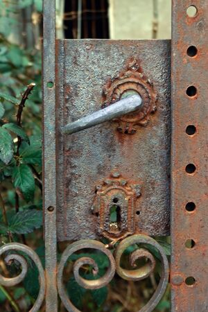 an old rusty metal lock on an abandoned house