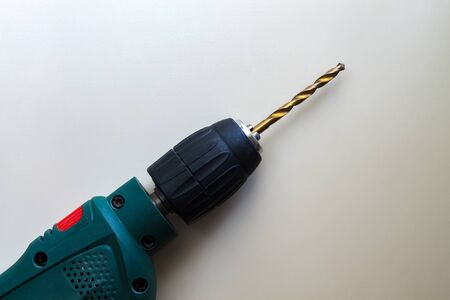 used electric green drill with metal drill bit inserted, ready for use