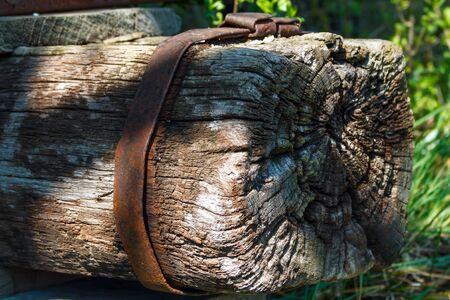 an old wooden pole with a rusty metal shackle Stock Photo