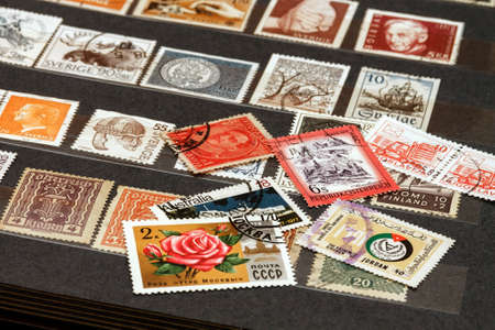 various old postage stamps from various countries in the philatelic album