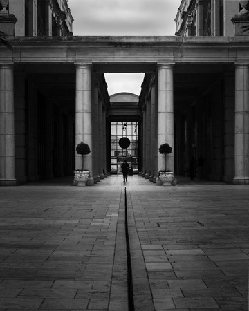 A lone figure walks away through a tunnel of grand architecture