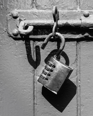 An unlocked padlock handing from a bolt and casting a defined shadow in black and white