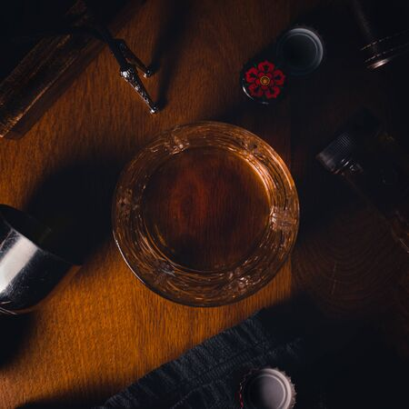 Top down flat lay image of a glass of bourbon whiskey surrounded by various bar accessories