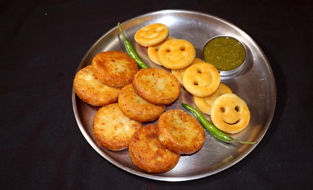 chaat: Snack made with potato - Aloo Tikki or fried potato patties and fried potato as smile shape ; a popular Indian snack.