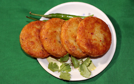 chaat: Aloo Tikki or Fried Potato Patties; a popular Indian snack served with tomato and chilli sauce. Stock Photo
