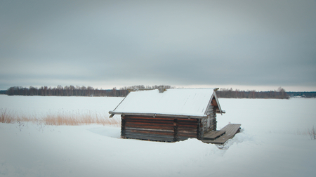 snowy field: Lonely wooden hut in the middle of a snowy field
