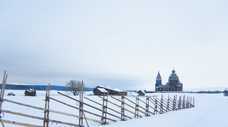 log cabin winter: Orthodox wooden Church in the village in the North of Karelia Stock Photo