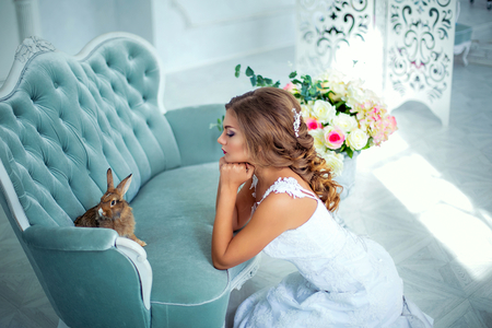 Beautiful, gentle bride in wedding dress with a rabbit on his hands