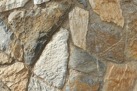 A stone wall of raw stone. Texture of stone. Stone wall.