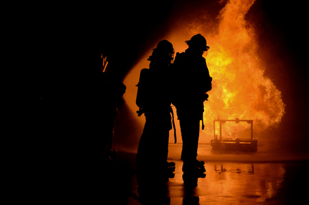 Fire fighter hosing water to extinguish a fire over the objects in accident on the factory