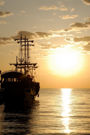 Pirates ship in the sea at sunrise photo