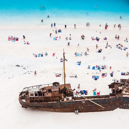 castaways enjoying sunbathing on white sand beach near shipwreck Stock Photo