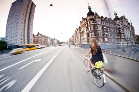 intentional: typical Copenhagen: pretty girl riding bike, old buildings around. Denmark