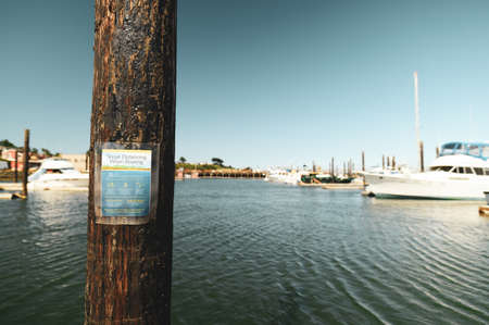 Social Distancing Guidelines sign on a pole in a harbor 스톡 콘텐츠