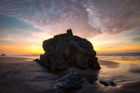 People sit on rock watching dramatic sunset at Oregon coast.