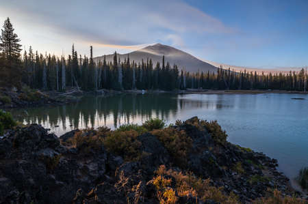 Smoke from distant wildfires 2020 surround Mt. Bachelor in Oregon. Sparks Lake in foreground.