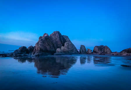 Beautiful rocks at beach reflect in wet sand during blue hour evening